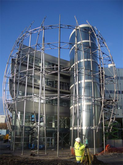 Sculpted solar veil of mesh panels and tubes sweeps around two